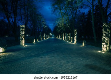 The tiled road in the night park with stone idols illuminated by lamps. Stone statues in the park at night. Illumination of a park road with lanterns at night. Lutsk