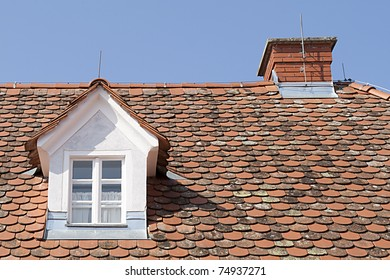 Tiled roof with attic windows and the chimney against the blue sky