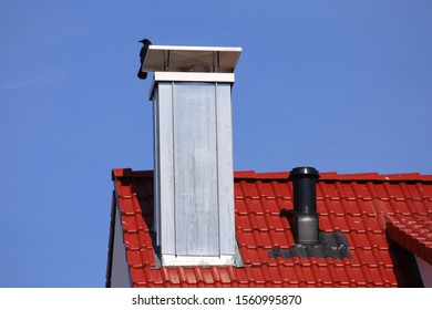 Tiled roof with chimney cladded with stainless steel