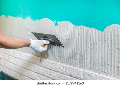 tiler applying tile adhesive on the wall
