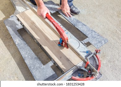 Tiler cutting a tile with a manual tile cutter. Artisan, craftsperson, gesture and movement of job, handiwork.