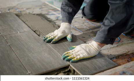 tiler is installing ceramic floor tiles above cement and electric floor heating, aligning, using building level, modern technology of repair, close up shot