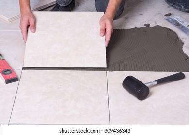Tiler installing ceramic tiles on a floor .