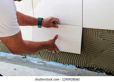 Tiler laying wall tiles in a bathroom