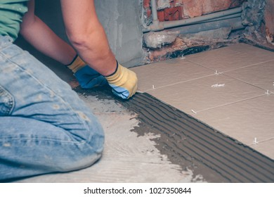The tiler puts his hands in yellow gloves square tile on the floor