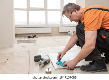 The tiler uses a caliper with a suction cup to drill holes in the ceramic tile.