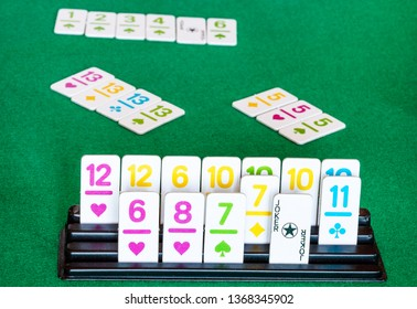 tiles in rack and board during playing in Rummy tile-based card game on green baize table. Rummy is tile and card game based on matching cards of the same rank or sequence and same suit