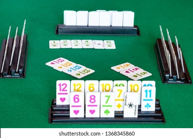 tiles in rack and gameplay in Rummy tile-based card game on green baize table. Rummy is tile and card game based on matching cards of the same rank or sequence and same suit
