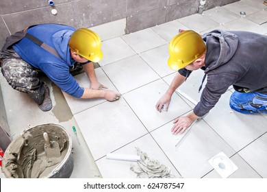 Tiling Floor & Wall. The tiler builder arranges the bathroom ceramics.