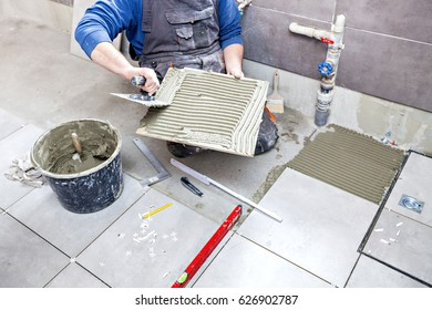 Tiling Floor & Wall. The tiler builder arranges the bathroom ceramics. Laying tiles on the floor