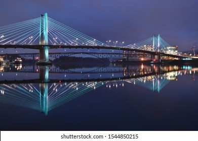 The Tillikum Bridge crosses the Willamette River in Portland, Oregon. The lights from the city's modern structures are reflected in the calm waters.