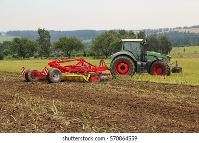 Tilling rape stubble with green tractor and red discs, preparation of soil in autumn for seeding wheat field certified as bio agriculture, cloudy day, back perspective