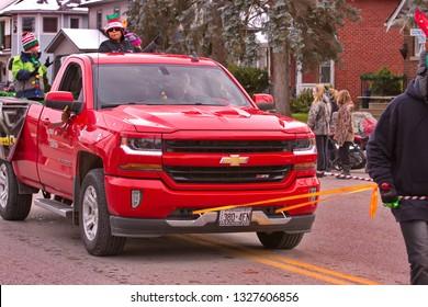 Tillsonburg, Ontario / Canada - November 17,  2018 :  Tillsonburg and Area Optimist Club Christmas Parade  showing a local Chevrolet Dealership's new red Chevrolet truck.