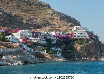Tilos, Dodecanese / Greece - August 15, 2017: Ilidi Rock Hotel on the seaside hill of the Tilos island. Blue surface of the Aegean Sea, beach, rocks, flowering shrubs.