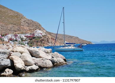 TILOS, GREECE - JUNE 12, 2018: A yacht enters Livadia harbour on the Greek island of Tilos. The small Dodecanese island is a popular sailing destination.