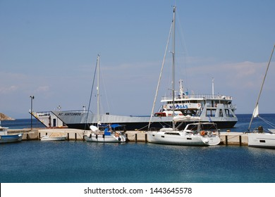 TILOS, GREECE - JUNE 12, 2019: Cargo ship Agios Antonios moored at Livadia harbour on the Greek island of Tilos. The 71.8mtr vessel was built in 1977 in Greece.