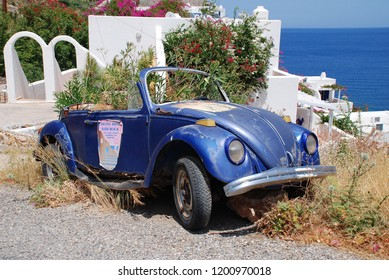 TILOS, GREECE - JUNE 15, 2018: An old abandoned Volkswagen Beetle car with plants growing inside at Livadia on the Greek island of Tilos. The Dodecanese island has a population of around 780 people.