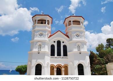 TILOS, GREECE - JUNE 18, 2018: Signage saying church of Agios Nikolaos (Saint Nicholas) on the seafront church at Livadia on the Greek island of Tilos. St. Nicholas is the patron saint of fishermen.