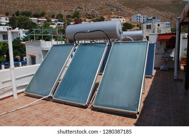 TILOS, GREECE - JUNE 21, 2018: A bank of solar heating panels on a roof top in Livadia on the Greek island of Tilos. The island aims to become self sufficient in energy from solar and wind sources.