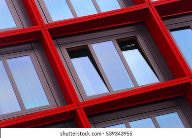 Tilt close-up photo of ajar windows in red frames. Optimistic abstract image on the subject of modern architecture. Residential or office building exterior detail.