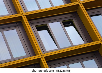 Tilt close-up photo of ajar windows in yellow frames. Residential or office building exterior detail. Optimistic abstract image on the subject of modern architecture.
