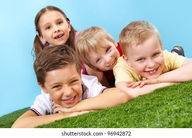 Tilt up of happy children having rest lying on the grass and looking at camera