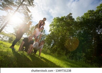 Tilt Image Of Happy Friends Making Human Pyramid In Forest