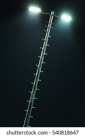 Tilt photo of glowing hi-tech street lamp at night. Stairs lead to the lamppost top. Fragment of modern urban architecture / cityscape. Luminous background for text placement.