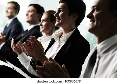 Tilt up of row of business people applauding to a successful speaker