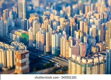 Tilt shift blur effect. Abstract futuristic cityscape with modern skyscrapers. Hong Kong aerial view evening panorama
