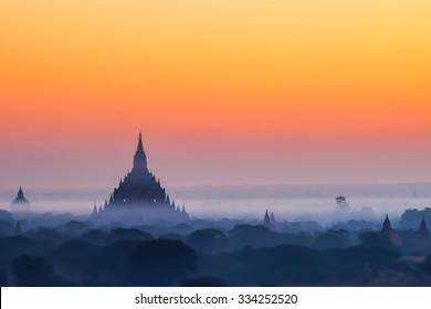 Tilt Shift blur effect. Amazing misty sunrise colors and silhouette of ancient Myauk Guni Pagoda. Architecture of ancient Buddhist Temples at Bagan Kingdom. Myanmar (Burma) travel destinations