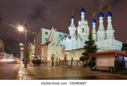 Tilt and shift view of night Moscow illuminated church with white walls and blue cupola in winter with car tracers and street lamps at long exposure