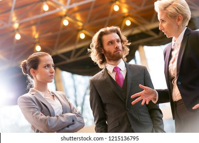 Tilt shot of mature businesswoman discussing with colleagues while standing at office