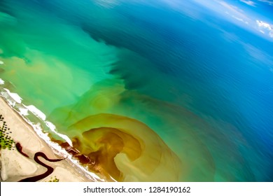 Tilted high aerial view of a river mouth bringing runoff into the ocean, making many layers of colors in concentric rings.