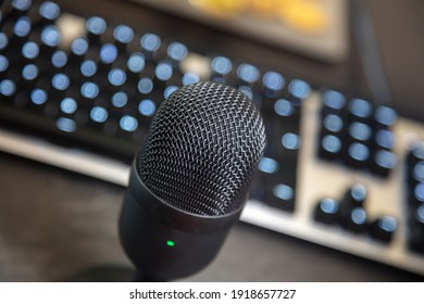 Tilted mic condenser black metallic, blur keyboard and monitor background. Digital technology concept. Communication with pc through mike, recording, radio, blogging. Close up, above view.
