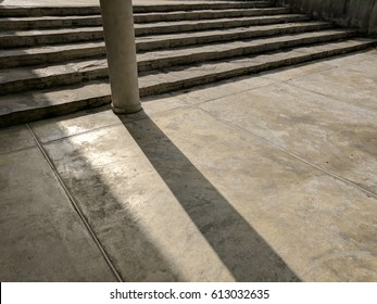 Tilted perspective view of stone concrete step stairs foot path and floor, walk way. The circle pole standing in the center and the shadow from the sun shading on, the texture of stone granite tile