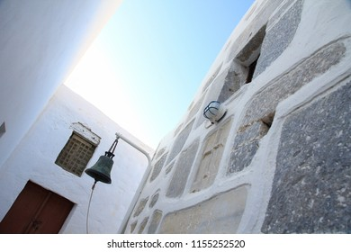 Tilted photo of a church bell in one of the narrow streets of Chora in Astypalaia island, Greece