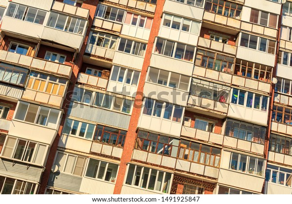 tilted photo with a large number of balconies on the wall of a multi-storey building. balcony of different design and glazing ugly design of the city