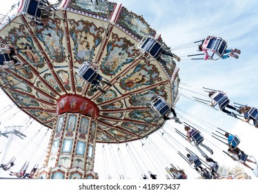 Tilting, swinging, aerial chair ride, full of people, at an amusement park