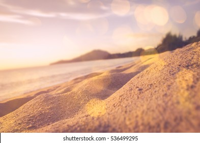 Tilt-shift blur tropical sunset sand beach with bokeh sun light abstract background. Copy space of outdoor summer vacation and business travel concept. Vintage tone filter effect color style.
