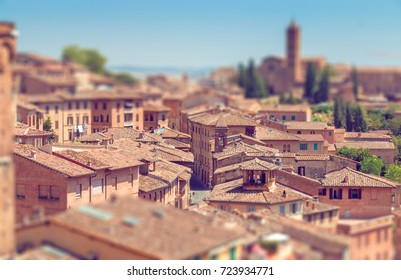Tilt-shift effect of beautiful italian town Siena with narrow lanes and streets and old roofs top view from above