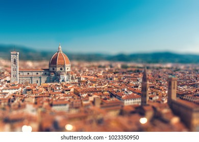 Tilt-shift miniature effect of beautiful italian town Florence with its symbol Santa Maria del Fiore in focus and old roofs top view from above