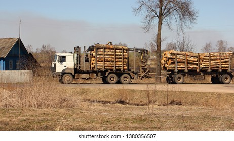 Timber carrier transports logs on a trailer on rural road on a spring day against a field and country house - commercial timber cutting, wood trading