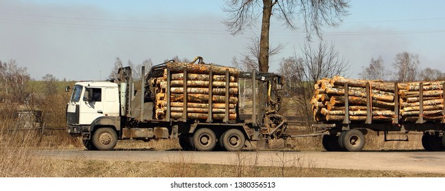 Timber carrying vehicle transports logs on a trailer on a country road on a spring day - commercial timber, wood trading