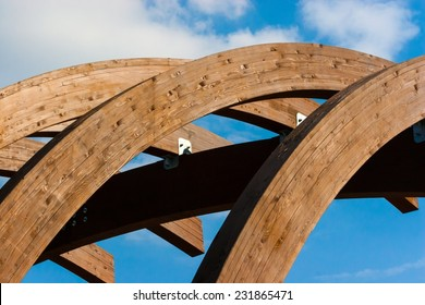 Timber frame arch against blue sky and white clouds midday.