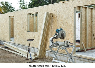 A timber frame house is constructed using OSB sheets to form timber panels. Carpenter's chop saw in the foreground