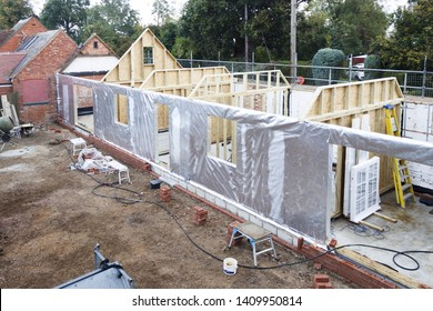 Timber frame house under construction with foil thermal insulation