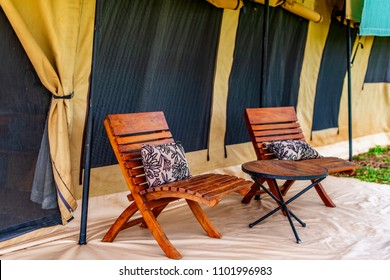 Timber outdoor chairs on the verandah of an exclusive, luxury safari tent. Window flaps are rolled up with mosquito, fly screens being visible. Serengeti NP, Tanzania, Africa.