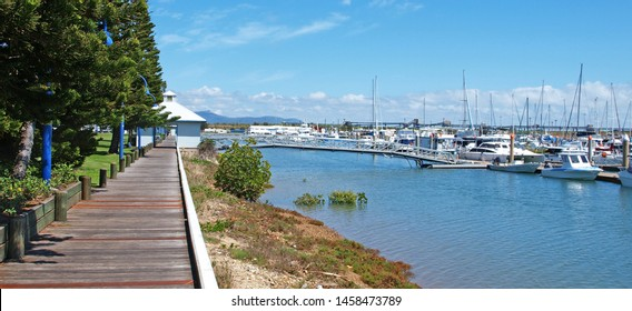 Timber waterfront boardwalk at picturesque Keppel Bay Marina with tropical water, boats, shrubs, and blue sky background. Safe haven for sailing and cruising vessels. The Great Barrier Reef,