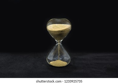 Time abstraction. Hourglass isolated on black background. Sand clock photo.